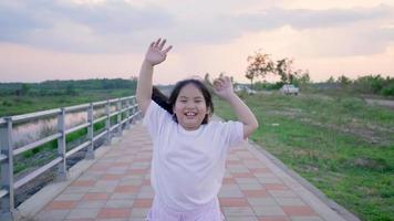 Asian girl running on the track with a smiling face and waving for the camera video
