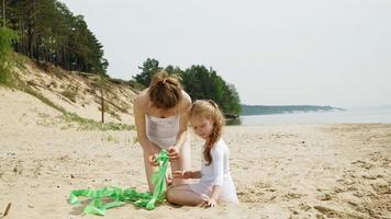 Mother and daughter in white bathing suits dancing with a gymnastic ribbon on a sandy beach. video