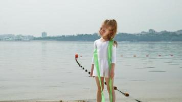 Preschool girl dances with a gymnastic ribbon on a sandy beach video