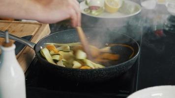 Cozinhe na cozinha cozinhando delicioso, vapor, comida saudável, dieta, filmagem de comida vegetariana video