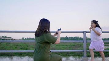 Asian mom taking a photo of her kid outdoors video