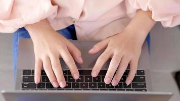 Vista superior de la mujer asiática que trabaja en la computadora portátil video