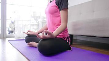 close-up de mulher asiática sentada em posição de lótus em um tapete de ioga video