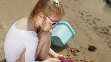 flickabarn leker med sand på stranden med hjälp av formfigurer solig sommardagssemester video