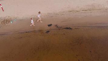 mor och dotter springer längs floden, luftfotografering video