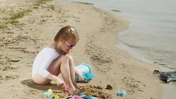 Niña juega con arena en la playa con moldes figurillas día soleado de verano vacaciones video