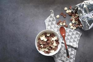 Top view of chocolate corn flakes in a bowl on pink photo