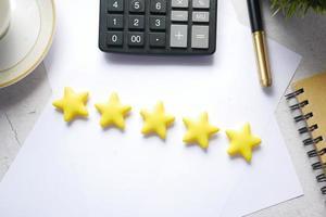concepto de revisión del cliente con calificación de estrellas doradas en la mesa foto