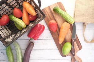 Selección de alimentos saludables con verduras frescas en una tabla de cortar en la mesa foto