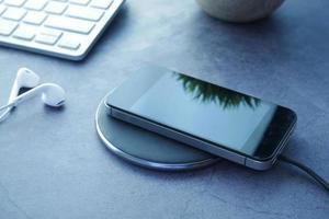 cargando el teléfono inteligente usando la plataforma de carga inalámbrica, vista superior foto