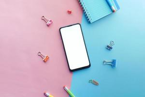 Top view of smart phone, notepad and stationary on color background o photo