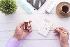 persona mano sujetando el contenedor de pastillas y el calendario foto