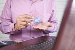 Joven aplicando líquido desinfectante antes de usar el portátil foto