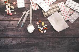 Drug addiction concept with heroine packet and syringe on black backgrund photo