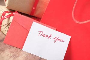 thank you message and envelope on wooden table photo