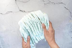 Hand holding stack of baby diaper on table photo