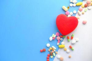 Heart shape symbol and pills on green background photo