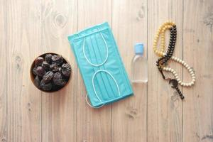 Fresh date fruit in a bowl , prayer rosary , hand sanitizer and mask on floor photo