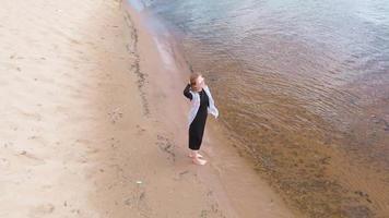une jeune femme vêtue d'une robe longe le tournage aérien de la plage video