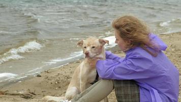 ung kvinna med en hund på stranden vid floden video