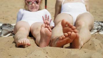 mamma och dotter solar på stranden. sommar, solig dag video