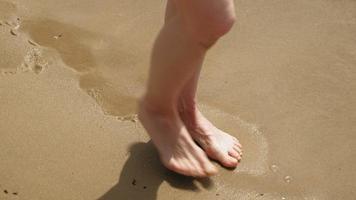 os pés estão na areia perto da água. praia dia ensolarado de verão video