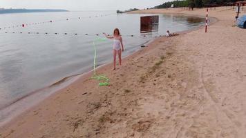 jovem ginasta vestindo uma roupa branca em uma praia de areia, dançando com fita de ginástica. video