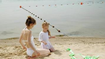 mãe e filha em maiôs brancos, dançando com uma fita de ginástica em uma praia arenosa. video