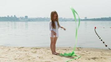 menina pré-escolar dançando com uma fita de ginástica em uma praia arenosa video