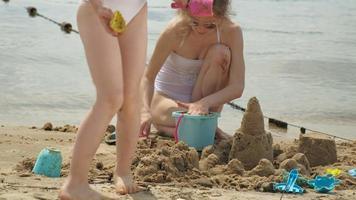 madre e hija jugando en la playa construyendo un castillo de arena video