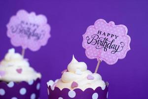 Cupcakes de vainilla con pequeños corazones decorativos y letrero de feliz cumpleaños, contra el fondo violeta de fondo de fiesta foto