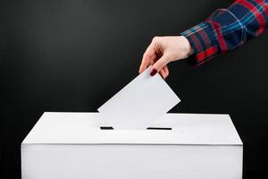 Elections and voting concept. Woman puts ballot paper in box on a black background. photo