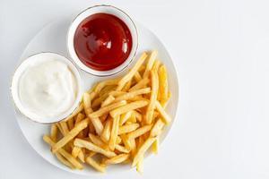 apetitosas papas fritas sobre fondo blanco. comida rápida caliente. lugar para el texto. foto