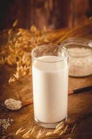 Glass of oat milk on a wooden background. photo