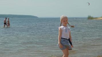 une fille marche au bord de la rivière un jour d'été video