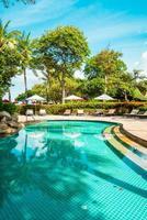 Hermosa playa tropical y mar con sombrilla y silla alrededor de la piscina en el complejo hotelero foto