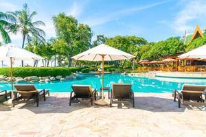 Hermosa sombrilla y silla alrededor de la piscina en el hotel y resort foto