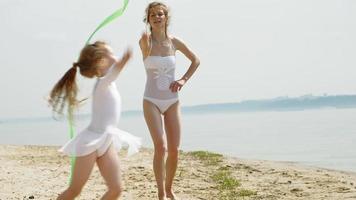 mor och dotter i vita baddräkter som dansar med ett gymnastikband på en sandstrand. sommargryning video
