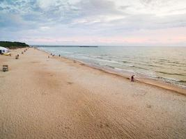 Palanga, Lithuania, 2019 - People walking on the beach in summer photo