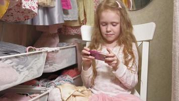 Beautiful little girl uses the phone video