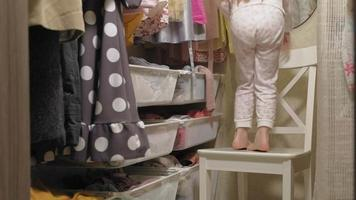 hermosa niña elige vestido de su armario de casa. belleza y moda video