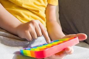 Colorful anti-stress sensory fidget push pop it toy in children's hands photo