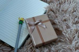 Gift box with a  ribbon and a Brown bow on a Wool carpet background. Selective focus. photo