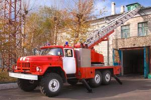 A large soviet red fire truck is preparing to leave photo