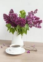 Bouquet of lilac flowers in a vase and cup of coffee photo