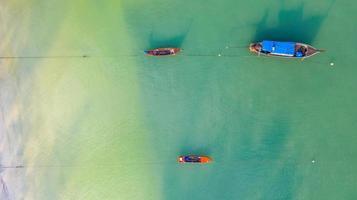 Vista aérea superior, barco de pesca, barco turístico flotando en un mar claro y poco profundo, hermosa agua azul brillante en el océano foto