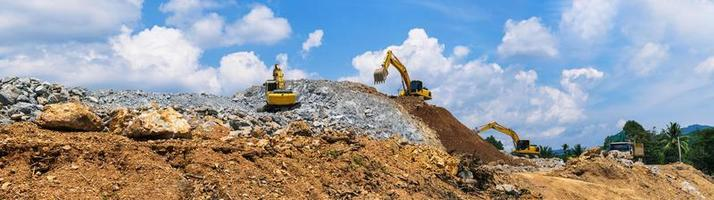 Panorama, Excavators and stone crushing machine of mining under a blue sky with clouds photo