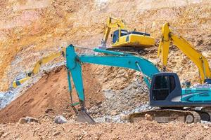 Excavators and stone crushing machine of mining under a blue sky with clouds photo