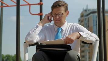 empresario mirando documentos en el área de ejercicio video