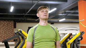 um homem fazendo um exercício no delta dorsal com halteres, sentado com as mãos retas em uma academia de ginástica video